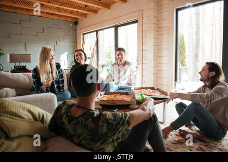 Groupe de jeunes heureux de manger des pizzas et se détendre dans la salle de séjour à la maison Banque D'Images