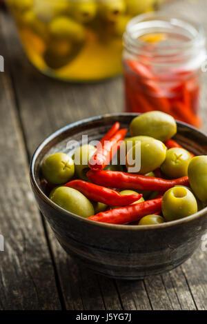 Piments marinés et olives vertes dans un bol. Banque D'Images