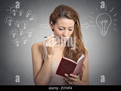 Belle fille portrait planification pensée écrit des notes isolées sur fond de mur gris Banque D'Images
