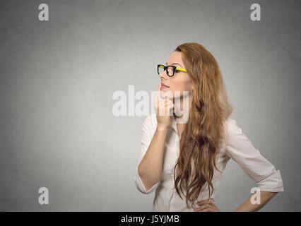 Portrait Portrait heureux belle femme penser à fond de mur gris isolé jusqu'à l'exemplaire de l'espace. Visage humain Banque D'Images