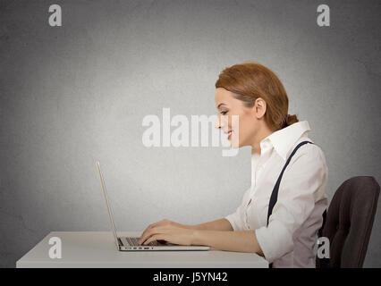 Voir le profil latéral libre attrayant à l'aide de son ordinateur portable gris fond Mur isolé. Cadre d'entreprise de travailler sur ordinateur, à l'emplacement h