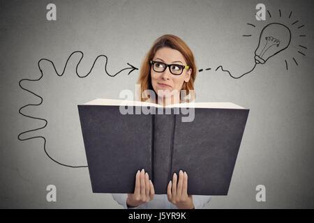 Femme lisant un livre énorme a une bonne idée Banque D'Images