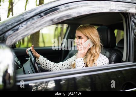Belle femme d'affaires parle sur le téléphone mobile et souriant tout en restant assis dans la voiture Banque D'Images