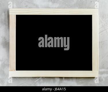 Tableau noir en blanc avec cadre en bois sur fond de béton.
