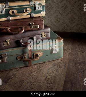 Pile de valises vintage en cuir, papier peint rétro sur l'arrière-plan. Banque D'Images