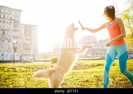 Fille avec chien avec stick Banque D'Images