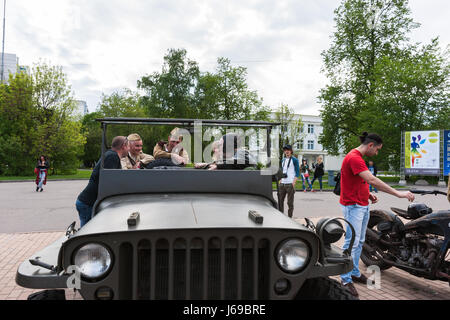 La Russie, Moscou. Samedi 20 Mai, 2017. Une exposition de voitures anciennes et des motos est en cours dans le parc d'attractions de Sokolniki. Environ 200 voitures et vélos sont exposés à l'air libre, y compris de nombreux véhicules automobiles et soviétique à partir de la Suède, l'Allemagne, les Etats-Unis, le Japon et les autres pays du monde. Beaucoup de personnes visitent l'exposition en dépit de l'outcast jour. Des personnes non identifiées dans l'uniforme militaire soviétique de guerre s'asseoir dans une voiture Vintage jeep Willis. Crédit: Alex's Pictures/Alamy Live News