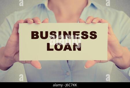 Business Woman hands holding white card signe avec business prêt message texte isolé sur fond de bureau mur gris. Banque D'Images