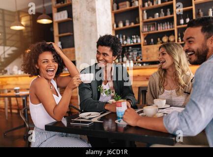 Heureux les jeunes gens assis autour de cafe table et boire du café. Groupe multiracial de friends enjoying coffee Banque D'Images