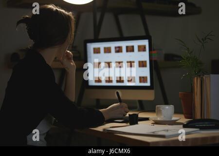 Vue arrière droit de concentré de jeune dame assise à l'intérieur de l'ordinateur à l'aide de designer et tablette graphique.