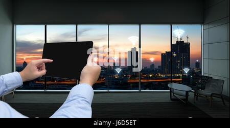 Internet des objets , l'Ito et réseau connexion concept. Businessman hand holding tablet noir fond coucher de soleil sur la ville et connexion Wi-Fi gratuite icônes