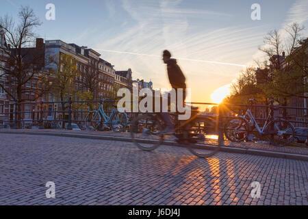 Vélo homme pont sur le canal Keizersgracht à l'aube, Amsterdam, Pays-Bas Banque D'Images