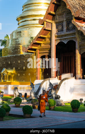 Jeune moine thaïlandais marcher en face de Wat Phra Singh Banque D'Images