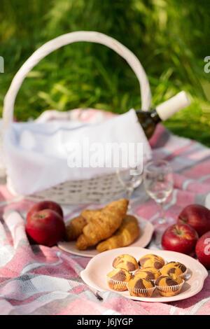 Pique-nique d'été dans la forêt sur l'herbe. Vin, fruits et croissants. Focus sélectif. Banque D'Images