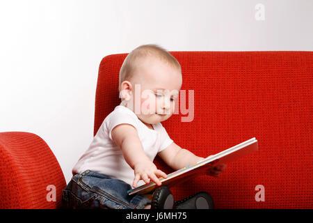 Heureux à l'âge de six mois, bébé garçon assis sur un canapé rouge, rendant les expressions faciales. Banque D'Images
