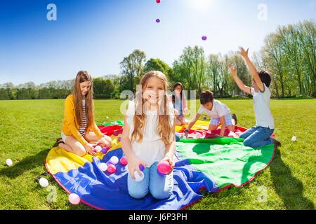 Portrait de la belle blondinette, assis sur le parachute et la tenue de boules colorées pendant le jeu avec des Banque D'Images