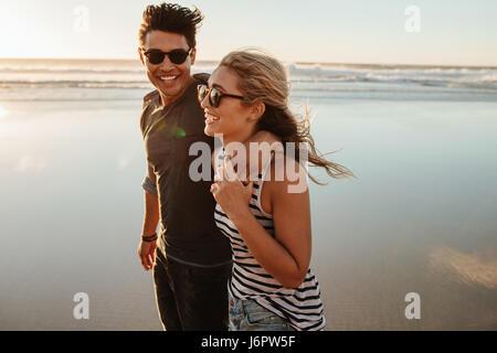 Portrait of young couple en train de marcher sur la mer. Homme et femme sur la plage de vacances pendant l'été. Banque D'Images