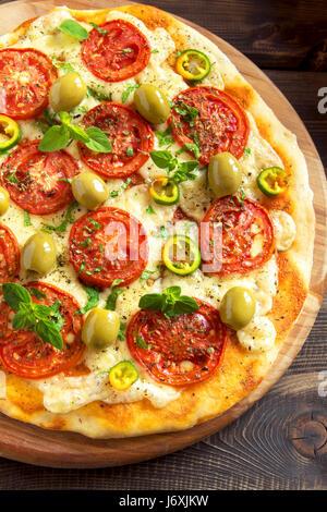 Pizza italienne avec tomates, poivrons, olives vertes, l'origan et de fromage mozzarella close up. Pizza aux légumes Banque D'Images