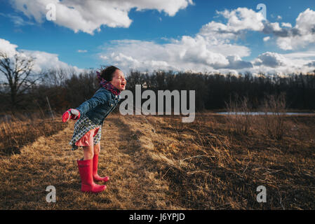 Girl with arms outstretched crier dans le vent