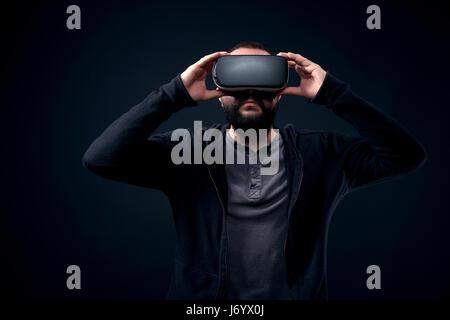 Jeune hipster barbu portant des lunettes de réalité virtuelle. fond noir studio concept vr Banque D'Images