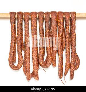 Rangée de saucisse de porc fumé dans des boyaux naturels accroché sur un poteau en bois pour sécher isolated on Banque D'Images
