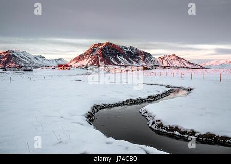 Paysage islandais dans laquelle on peut voir un groupe de maisons et le voyant rouge du soleil sur les montagnes Banque D'Images