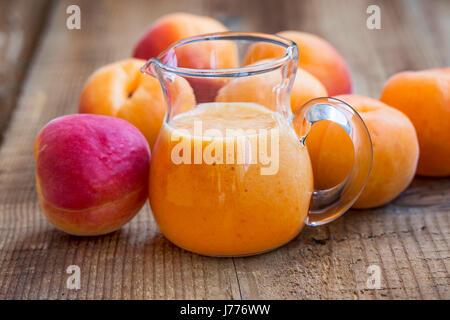 Smoothie aux fruits abricots sur planche de bois Banque D'Images