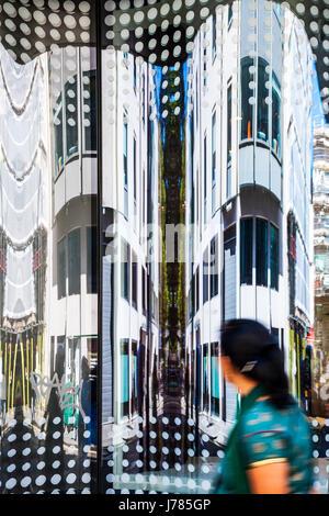 Femme asiatique en passant devant un immeuble de bureaux à la recherche à l'image déformée par la réflexion dans Banque D'Images