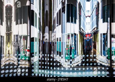 Reflets déformés dans la fenêtre d'un immeuble de bureaux modernes à Soho, Londres. Banque D'Images