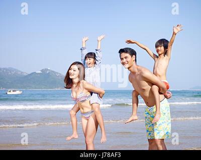 La famille asiatique avec deux enfants s'amusant sur la plage. Banque D'Images