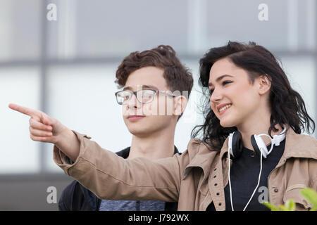 Deux smiling Young boy and girl planning à regarder autour et visiter la ville. Elle lui montre où est le lieu de Banque D'Images