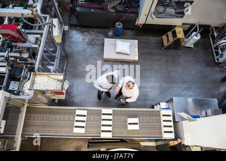 Vue de dessus deux hommes avec tablet parler dans l'atelier d'usine Banque D'Images