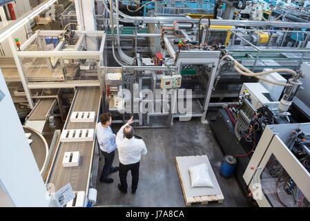 Vue de dessus deux hommes parlant dans l'atelier d'usine Banque D'Images