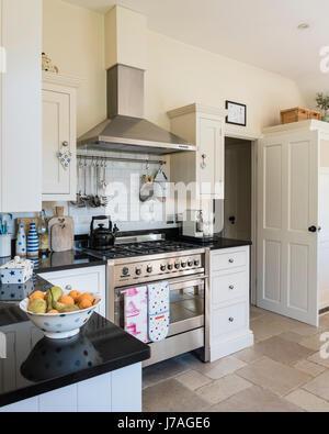 Grande cuisine ouverte avec cuisinière Smeg et carrelage rustique. Les unités sont peint en blanc de la terre tiré Banque D'Images