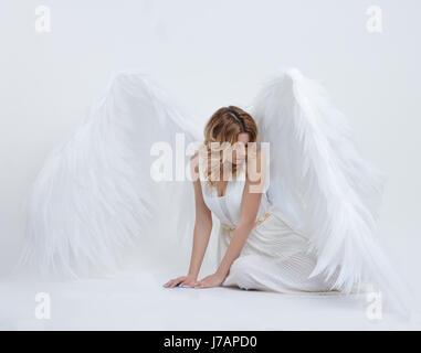 Beau jeune modèle avec de grandes ailes d'anges assis dans le studio Banque D'Images