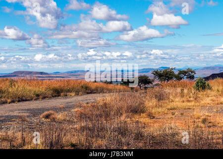 Rural vide chemin de terre qui traverse le paysage sec de l'hiver contre ciel nuage bleu horizon n'Etat libre d'Orange Banque D'Images