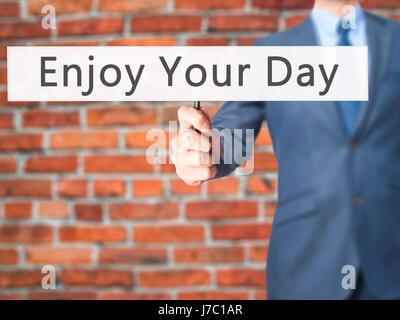 Profitez de votre journée - Businessman hand holding sign. Le commerce, la technologie, internet concept. Stock Photo
