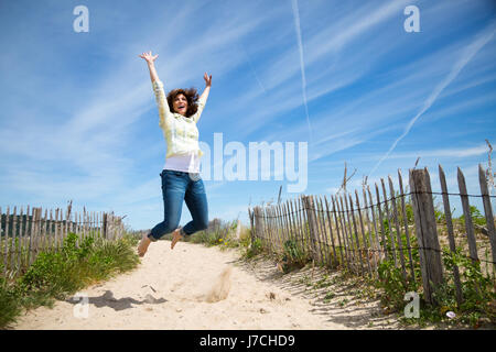 Happy young woman jumping on the beach crazy for locations Banque D'Images