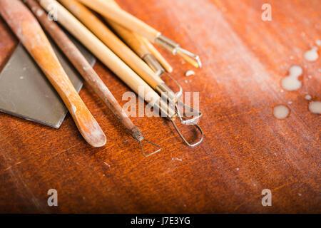 Atelier de poterie, céramique, concept art - gros plan sur les outils de sculpture situé sur une table en bois, Banque D'Images