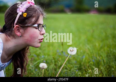 Belle fille blonde assise sur une belle herbe verte et pleine de fleurs de pissenlit le soufflage bénéficie d'oranger, Banque D'Images