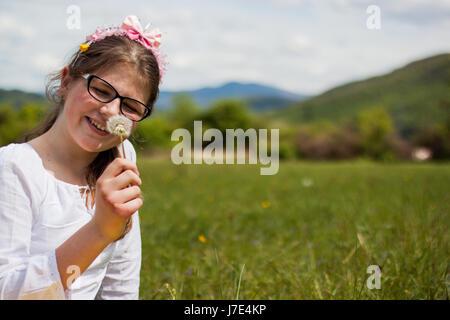 Belle fille blonde assise sur une belle herbe verte pleine de fleurs et de profiter tout en observant les fleurs Banque D'Images