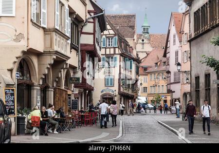 Les gens marcher dans et assis dans des cafés à l'époque médiévale à colombages - maintenant des maisons et des Banque D'Images