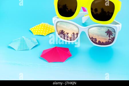 dd7df095c5c53b ... Lunettes colorées et parasol sur fond bleu clair studio avec palmier  réflexion sur les vacances d