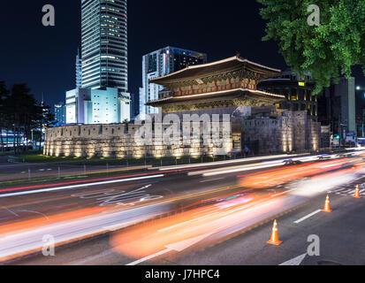 Trafic, capturé avec blurred motion, se précipite à travers le porte Dongdaemun la nuit à Séoul, Corée du Sud capitale. Banque D'Images