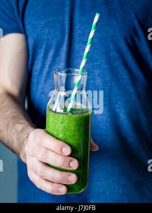 Smoothie vert. Man hands holding bouteille avec des smoothie vert detox. Vue rapprochée, selective focus