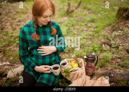 Fille enceinte dans les bois sur un pique-nique Banque D'Images
