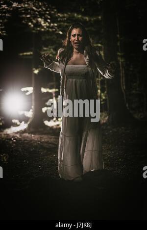 Jeune femme peur marche à travers la forêt la nuit en robe blanche et crier. Scène d'horreur. Banque D'Images