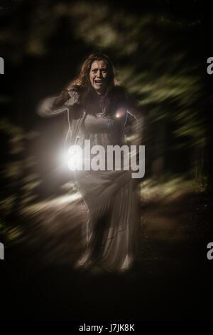 Jeune femme effrayée qui traverse la forêt la nuit en robe blanche et crier. Scène d'horreur. Banque D'Images