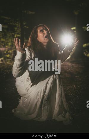 Jeune femme criant peur dans la forêt la nuit en robe blanche. Banque D'Images