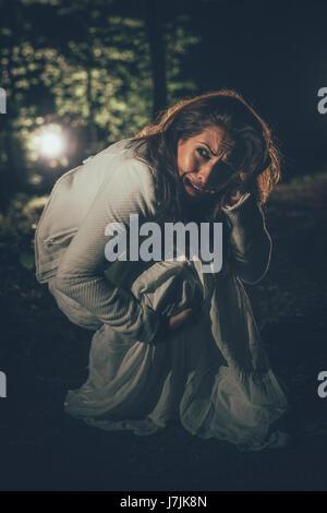 Les jeunes peur femme perdue dans la forêt la nuit en robe blanche. Banque D'Images
